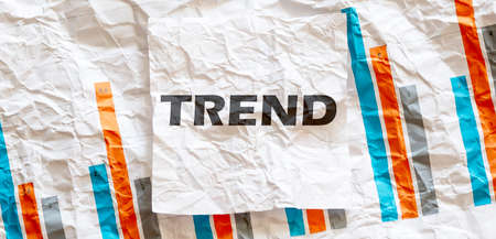 TREND word text on the white memo note crupled sticker on chart background