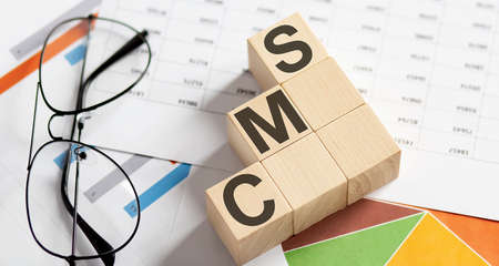 CMS words with wooden blocks on chart background. Business concept.
