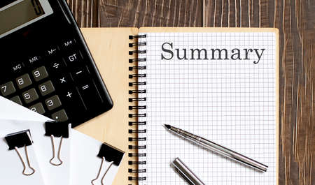 Notepad with text SUMMARY on wooden background with clips, pen and calculator Stock Photo