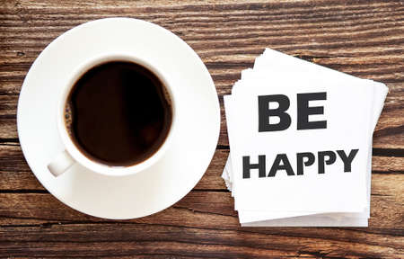 Word writing text BE HAPPY. Business concept for Urgent Move.Text in white stickers with a cap of coffee