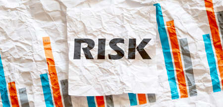 RISK word text on white memo note crupled sticker on chart background