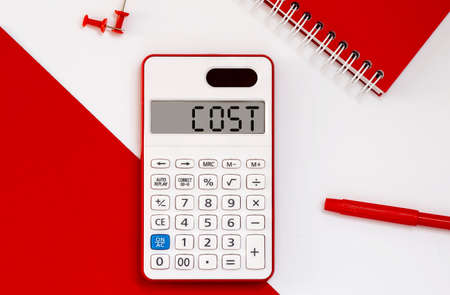 calculator with the word COST on display with red notepad and office tools Reklamní fotografie