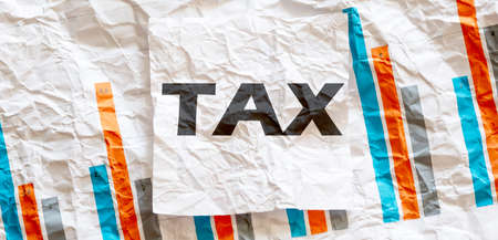 TAX word text on white memo note crupled sticker on chart background