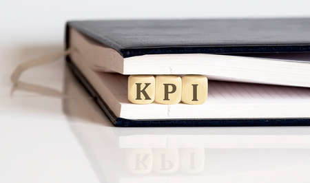 KPI on wooden cubes in notepad on the white background