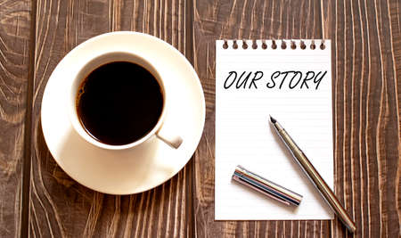 OUR STORY - white paper with pen and coffee on wooden background. Business