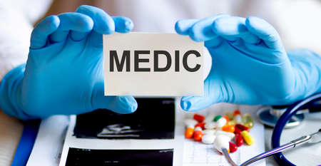 text MEDIC write on a medicine card. Medical concept with a stethoscope, pills Stok Fotoğraf