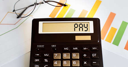 calculator with the word PAY on display with chart and glasses