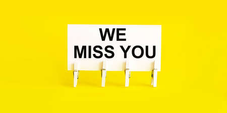 text WE MISS YOU on the white short note paper yellow background