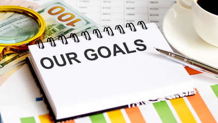 OUR GOALS text. Business graph marketing plan have book, pen, black coffee, paper clip, magnifier and dollars