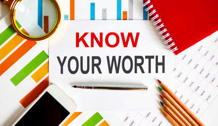 Text Know Your Worth on notepad with office tools, pen on the financial report