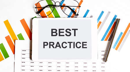 The tablet with text best practice on the business charts and pen