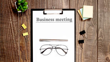 Business reports, blank paper sheet - directly above view of office table workspace BUSINESS MEETING text. Archivio Fotografico