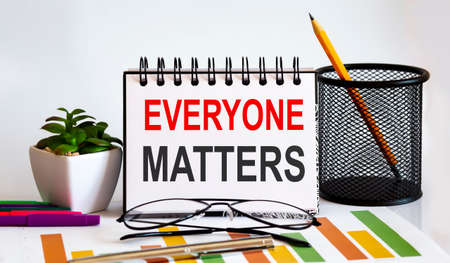 Everyone Matters word with Notepad on white background with markers, charts and glasses. Business concept