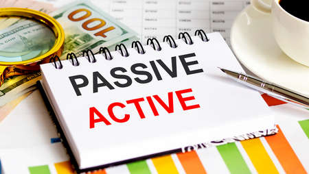 PASSIVE ACTIVE text.Top view office table, Business graph show for marketing plan have book, pen, black coffee, paper clip, magnifier and dollars, business