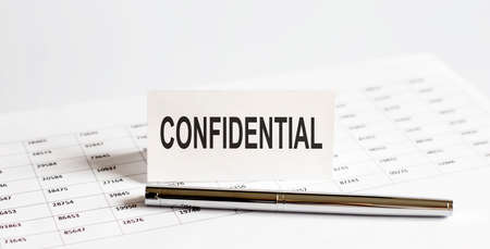 Text CONFIDENTIAL on stickers, pen on the background of documents. Financial bookkeeping, Accounting Concept.