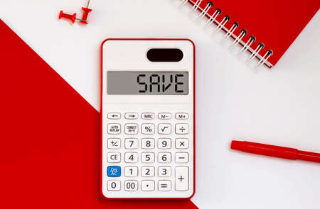calculator with the word SAVE on display with red notepad and office tools 免版税图像