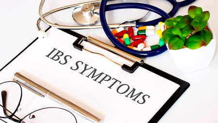 IBS SYMTOMS text with Background of Medicaments, Stethoscope Standard-Bild