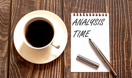ANALYSIS TIME - white paper with pen and coffee on wooden background. Business 免版税图像