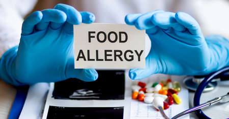text FOOD ALLERGY write on a medicine card. Medical concept with a stethoscope, pills