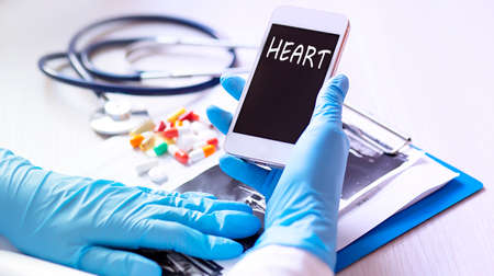 Close up hands doctor take smartphone with text HEART tablets, stethoscope, healthcare. Banco de Imagens