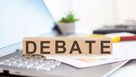 DEBATE Wooden cubes with letters on a laptop keyboard with charts, magnifier Stockfoto