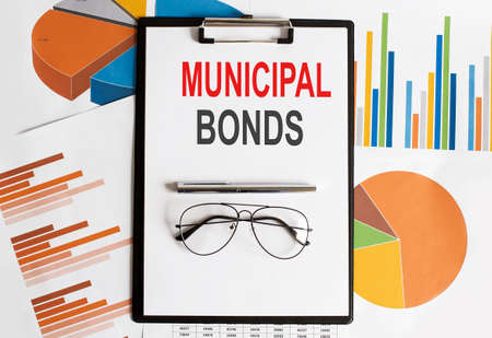 MUNICIPAL BONDS text. Conceptual background with chart, papers, pen and glasses