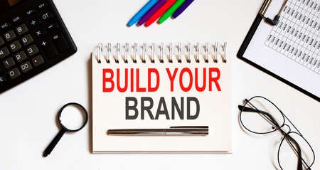build your brand text written on notebook with pencils and office tools