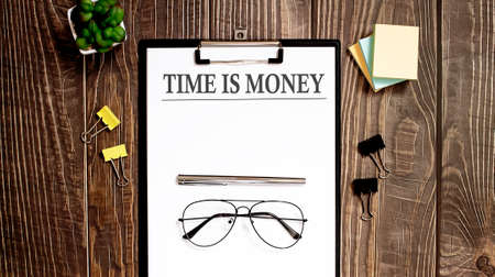 TIME IS MONEY text form on wooden table with office tips