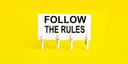 text Follow The Rules on white short note paper yellow background Фото со стока