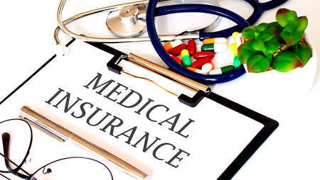 MEDICAL INSURANCE text with Background of Medicaments, Stethoscope Standard-Bild