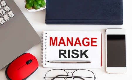 Manage Risk text written on notebook with pencils