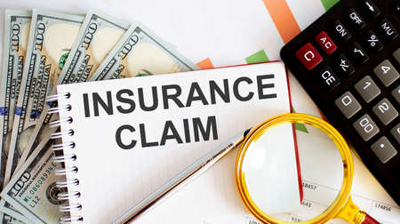 Word writing INSURANCE CLAIM. Business concept with chart, dollars and office tools
