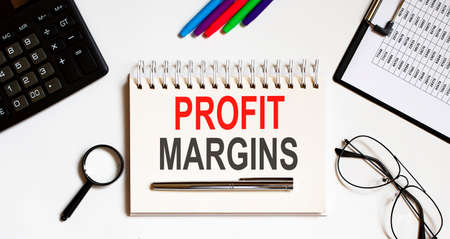 PROFIT MARGIN text written on notebook with pencils and office tools