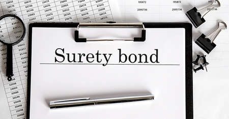 Paper with text SURETY BOND on table