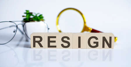 wooden word block RESIGN on white background with glasses and magnifier