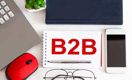 B2B text on notepad, pen, office tools on the white background. Business 스톡 콘텐츠