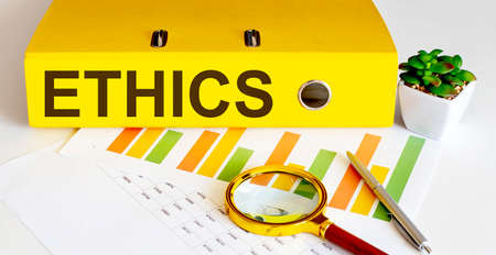 office folder with text ETHICS on charts, magnifier and pen