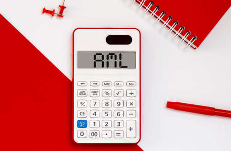 calculator with the word AML on display with red notepad and office tools