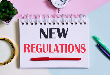 New Regulations text written on notebook with pencils, magnifier