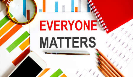 Everyone Matters text on paper with office background and chart