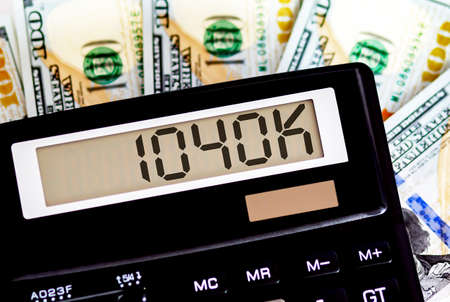 Calculator with text 1040 k on dollars. Business, finance conceptual.