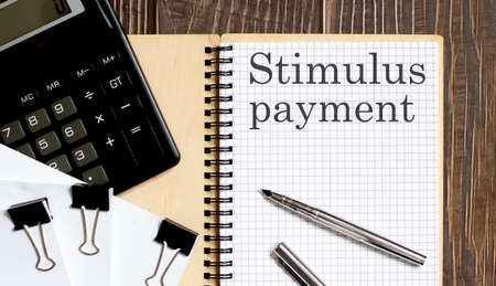 Notepad with text stimulus payment on wooden background with clips, pen and calculator