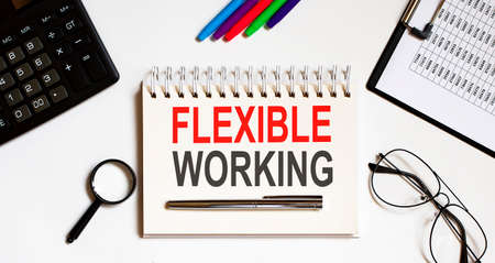 FLEXIBLE WORKING text in the office notebook with office tools, business