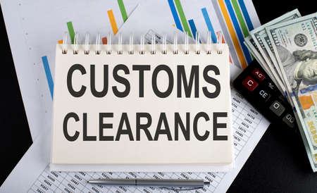 Customs Clearance text written on notebook with chart, calculator and dollars Фото со стока