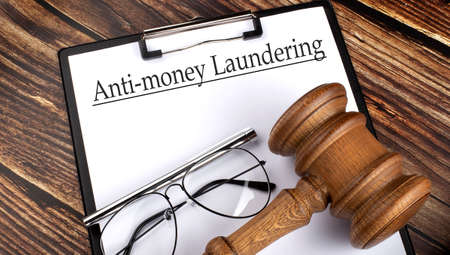 Paper with Anti-money laundering AML with gavel, pen and glasses on the wooden background