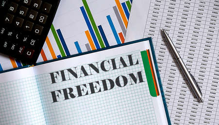 Closeup of notebook with text Financial Freedom on chart background. 版權商用圖片