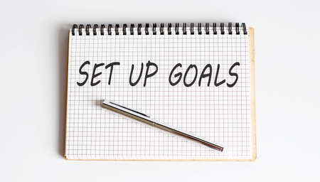 Notebook with pen and Notes about SET UP GOALS on white background