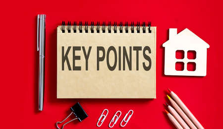 KEY POINTS text written on red background on a notebook with pencils and office tools and model wooden house