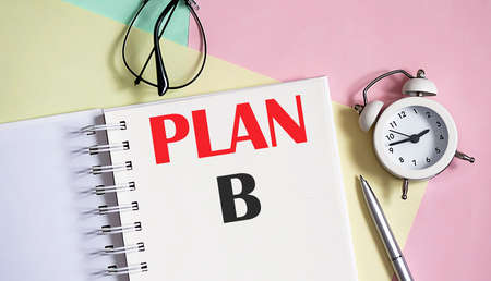 plan B on notebook with pen, alarm clock on the pink background