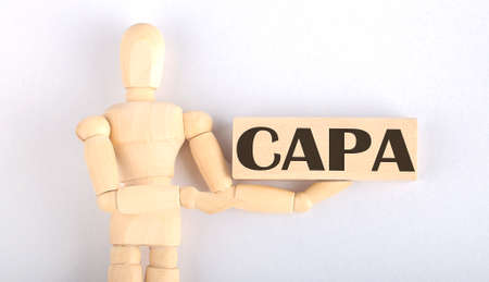 Wooden man shows with hand to block with text CAPA